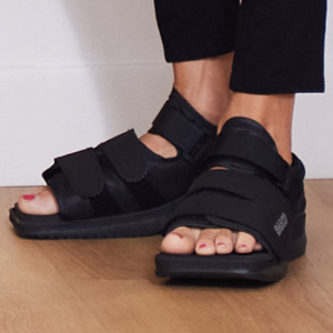 Patient wearing surgical sandals immediately after bunion surgery on both feet