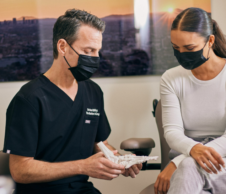 Dr. Blitz and patient in masks reviewing a model foot