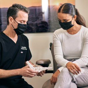 Dr. Blitz an patient in masks reviewing foot model