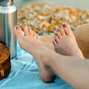 Woman's resting her bare feet on a blanket at the beach