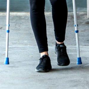 Teenager walking on crutches
